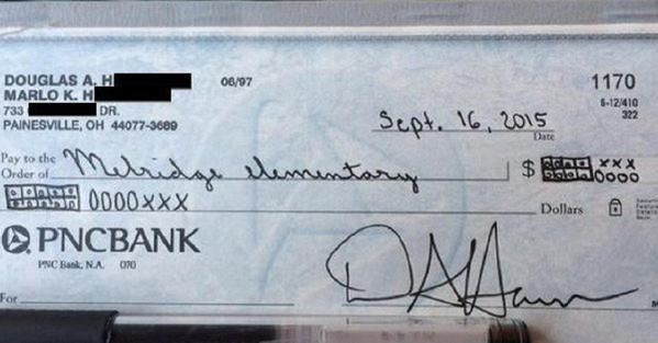 Dad writes donation check to school